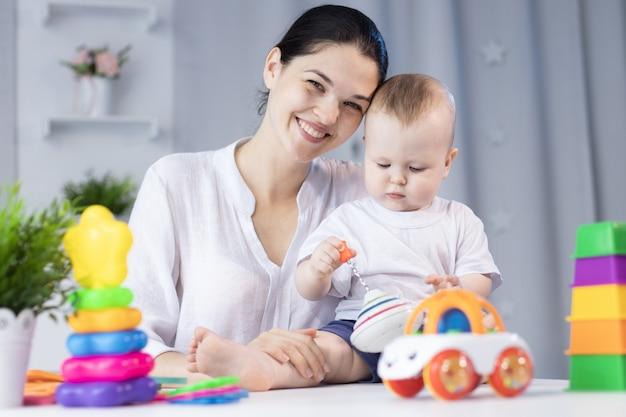 Мать и ее очаровательный новорожденный ребенок в светлой комнате