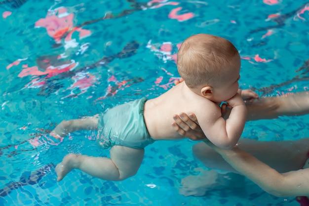 Малыш с мамой учатся плавать в бассейне