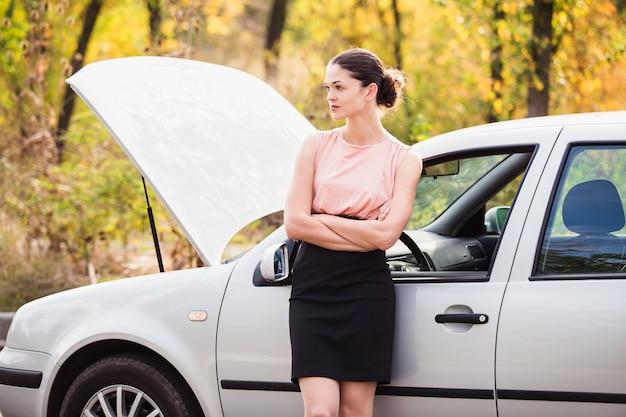 女性が車の近くで道端で分解された援助を待つ