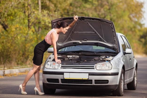 若い女性が車のボンネットの下を見て、破損の原因を見つけようとしている