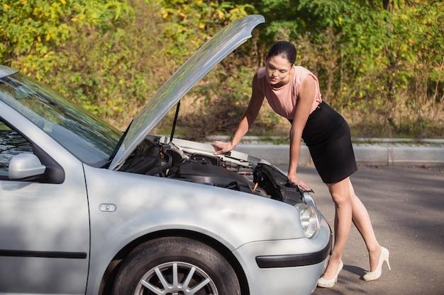 若い女性が車のボンネットの下を見て、車が故障したために避難を引き起こした