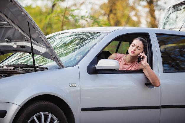 避難所を呼び出す若い女性。彼女の車は道路で故障した。