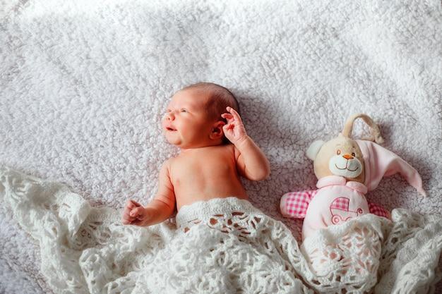 生まれたばかりの赤ちゃんは透かし彫りの毛布の下でクマと一緒に横たわっています