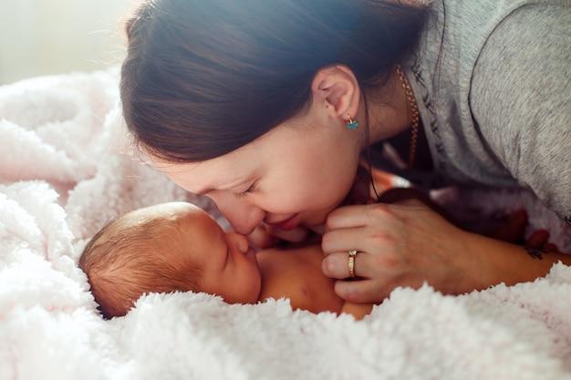 ママと白い壁に生まれたばかりの赤ちゃん