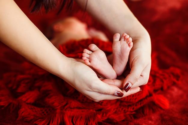 ママは赤い表面に生まれたばかりの赤ちゃんの足を保持します