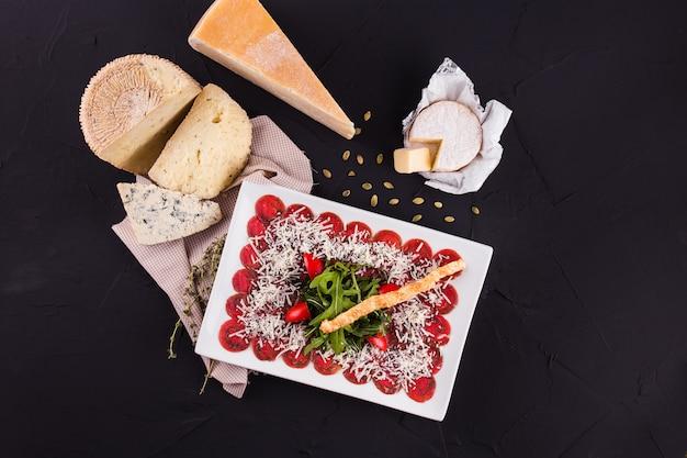 さまざまな種類のチーズの大きな部分が描かれた黒い表面(上面図)の装飾が施された長方形のプレート上のサラダ