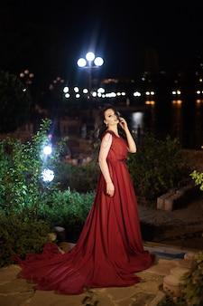 夜の公園でポーズをとる電車で赤いドレスを着た若いブルネットの女性