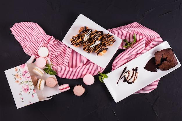 黒い表面にデザート。マカロン。醸造ケーキ。アイスクリーム。チョコレートパン。上面図。