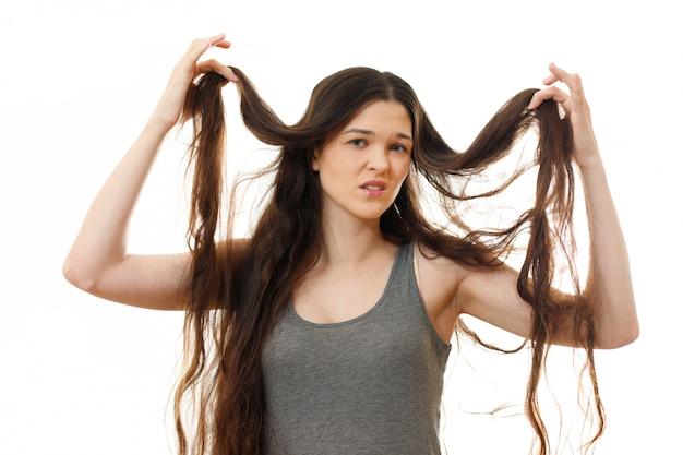 Молодая женщина с проблемными волосами. на белом изолированные