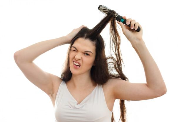 Молодая женщина не может расчесывать проблемные спутанные волосы. на белом фоне крупным планом