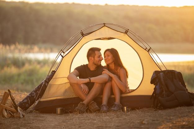 夕暮れ時、テントに男と女が座っています。ハイキングのハネムーン