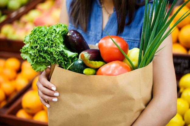 店の棚に女性の手で野菜と果物が入ったクローズアップの紙袋