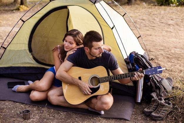 夕暮れ時にテントの近くでギターを弾く男性が女性のために演奏します。ハイキングのハネムーン