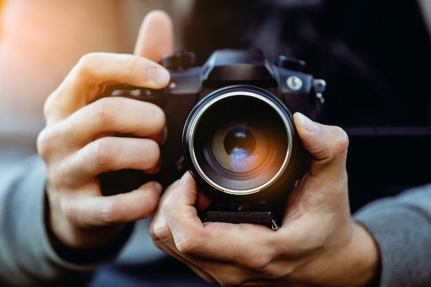 カメラは太陽フレアを持つ男性カメラマンの手に近い