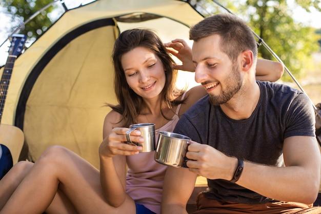 キャンプ旅行中の男女がテントのそばに座ってお茶を飲む。