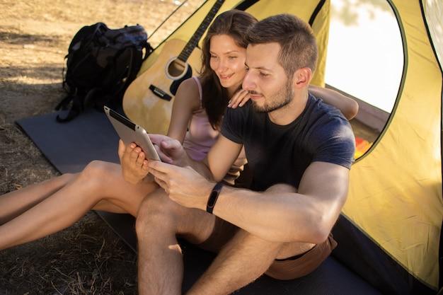 タブレットでテントの近くの男女。彼らは友達とビデオコミュニケーションについて話します