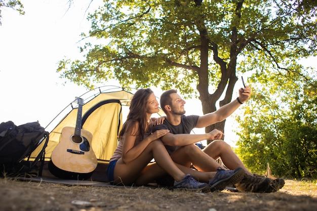 キャンプ旅行中の男女がテントの近くで自撮りをします。