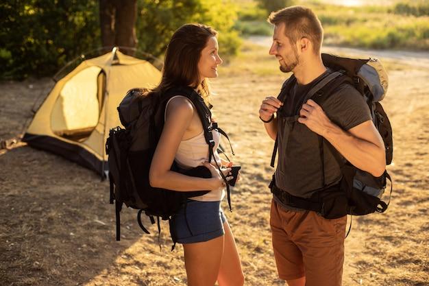 夕暮れ時のテントの近くのバックパックでハイキング旅行の男女。自然の中の新婚旅行