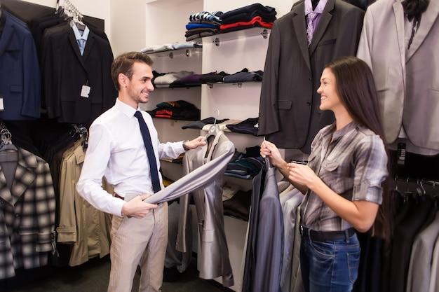 女の子の売り手はジャケットメンズウェアブティックでクライアントをピックアップするのに役立ちます