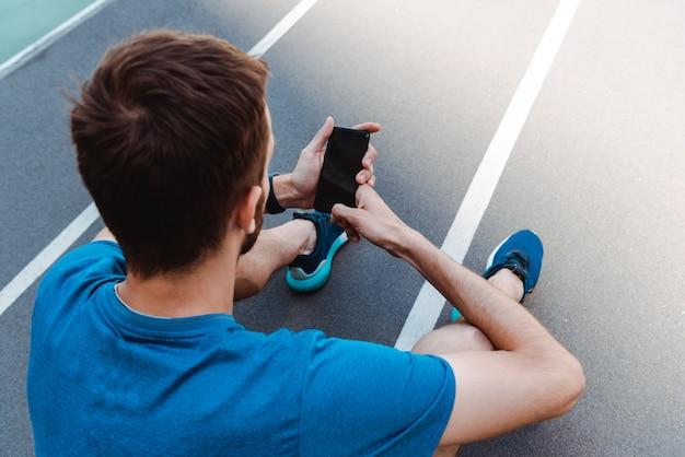 Вид сзади молодого спортсмена, сидя на беговой дорожке и с помощью смартфона