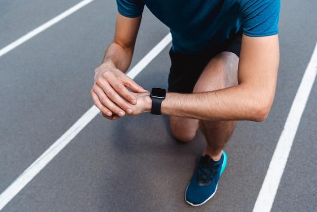 Частичный вид спортивного молодого спортсмена, смотрящего на умные часы на беговой дорожке