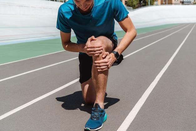 Частичный вид спортивного молодого спортсмена касаясь ноги на беговой дорожке