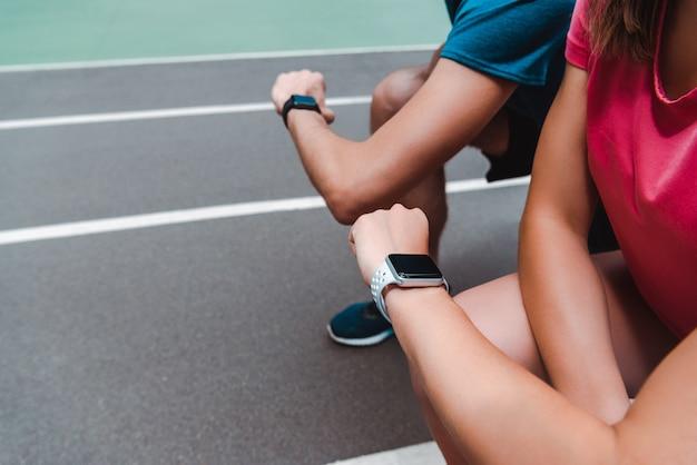 Частичный вид спортивной пары, глядя на часы на беговой дорожки в солнечный день
