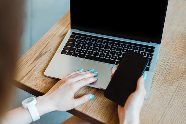 カフェの木製テーブルでスマートフォンの近くのノートパソコンのキーボードで入力する腕時計の女性の部分的なビュー
