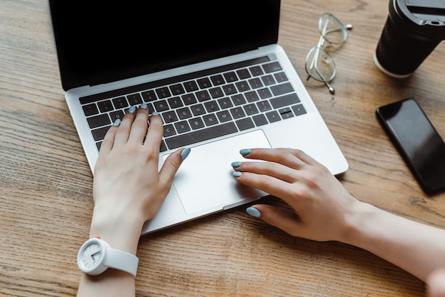 スマートフォンとコーヒーの近くのノートパソコンのキーボードで入力する女性のトリミングビュー