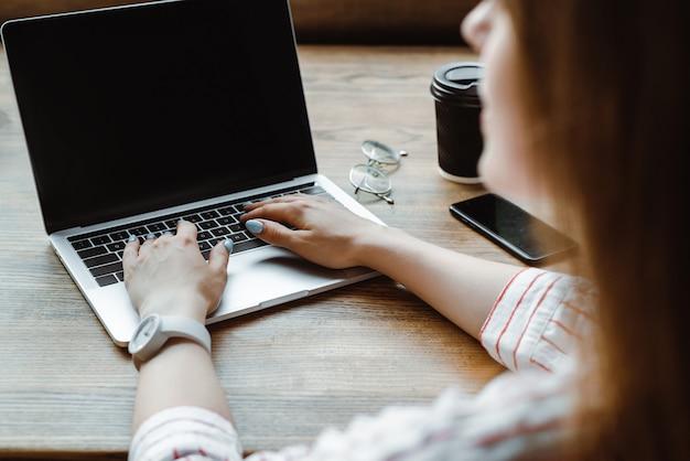 スマートフォンとコーヒーの近くのノートパソコンのキーボードで入力する女性の選択と集中は、カフェの木製のテーブルに行く