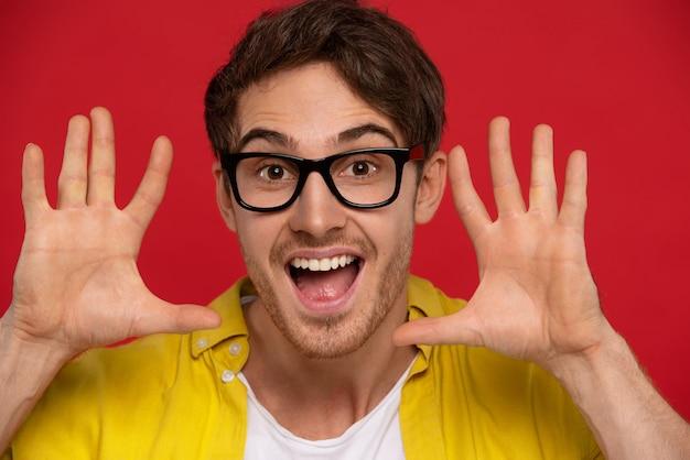黄色いシャツと口を開けて手を見せて眼鏡をかけた興奮した男は、うれしそうな表情をしていて、