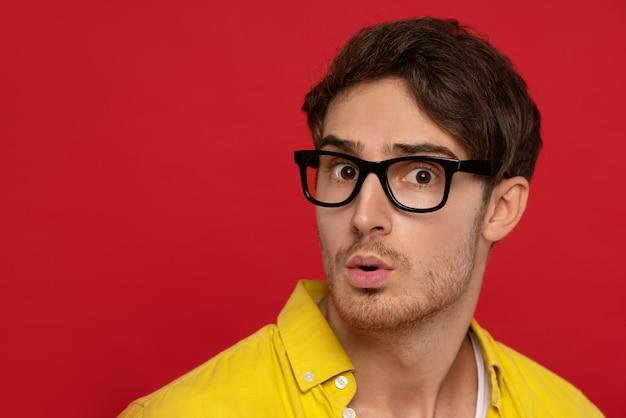 黄色のシャツとメガネでショックを受けた男
