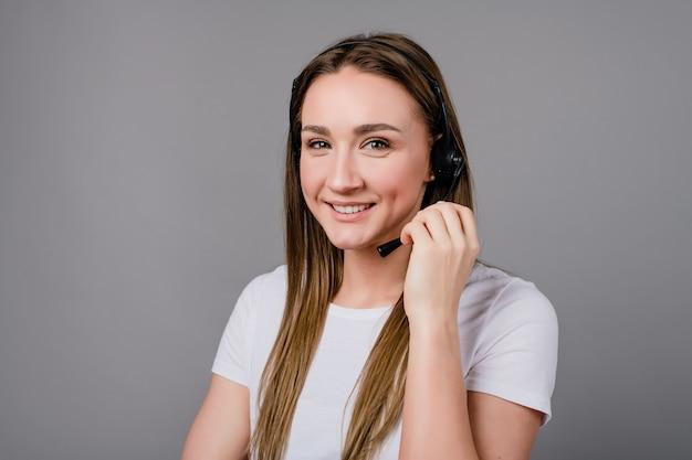 灰色に分離された電話に答えるワイヤレスヘッドセットに笑みを浮かべて女性
