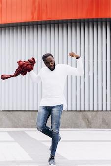 カジュアルな服を着て、グランジのコンクリートの壁の背景で踊るハンサムアフロアメリカ人。