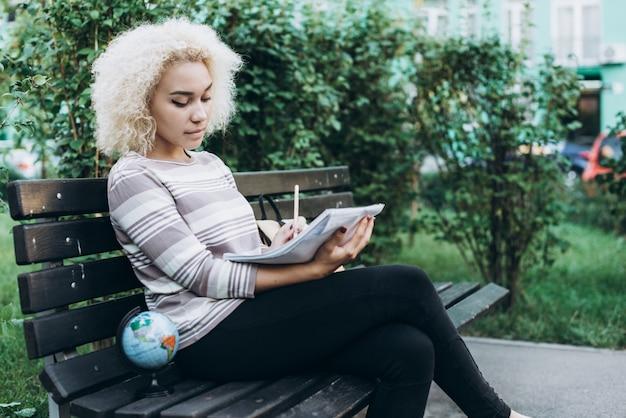 Веселая молодая студентка на открытом воздухе сидит на скамейке