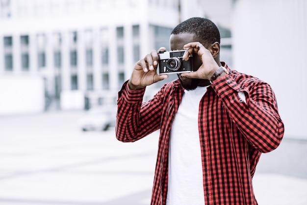 屋外の夏の笑顔のライフスタイル肖像画ハンサムで幸せアフロアメリカの観光客がカメラでヨーロッパの街で楽しむ旅行写真のヒップスタースタイルで写真を撮る