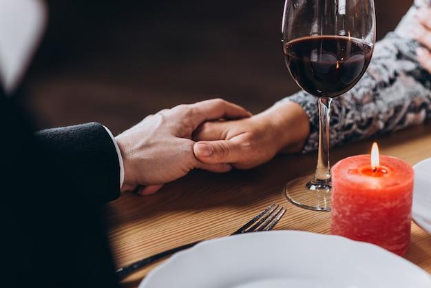 レストランのクローズアップのテーブルで手を繋いでいる中年の愛情のあるカップル