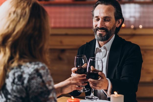 中年の愛情のあるカップルはロマンチックな夕食を食べます