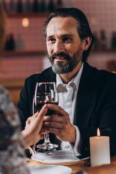 中年の男性は喜んで微笑んで女性と一緒に赤ワインのガラスを育て