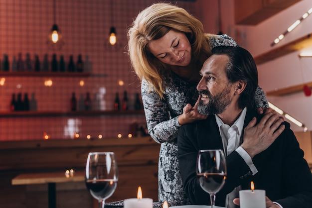 女性は彼の肩に彼女の手を持つ男の後ろに立ち、手は頬に触れます