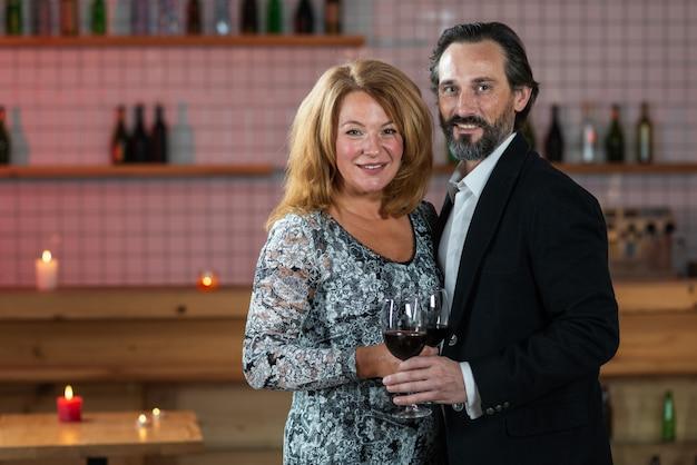 中年の男性と女性が上げられたグラスワインで立って、カメラをのぞきます