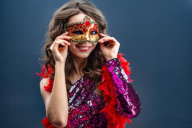 カーニバルマスクときらびやかなドレスを着た女性が笑っています。