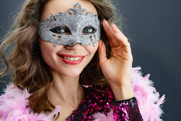 カメラのクローズアップを見てカーニバルマスクで笑顔の女性の肖像画