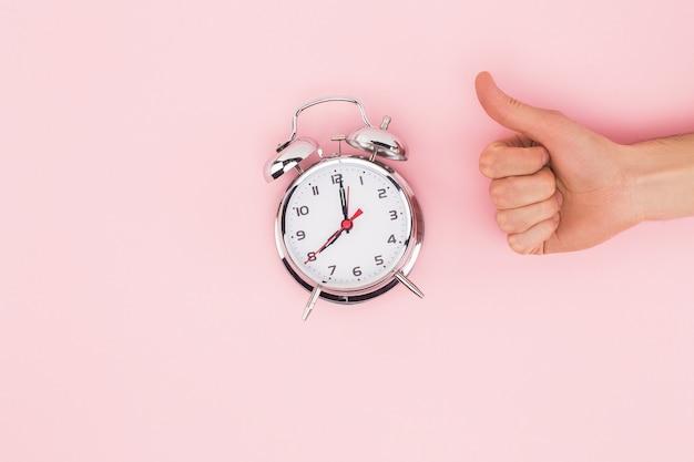 Обрезанное мнение человека, показывая большой палец вверх знак возле будильника, изолированных на розовом