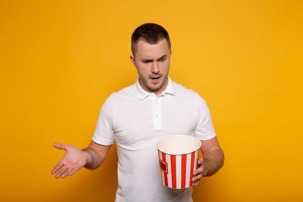 Смущенный человек, держащий пустое ведро для попкорна и показывающий жестом на желтом
