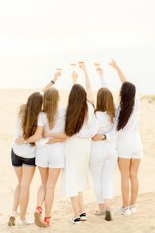 Пять девушек обнимаются на пляже и пьют коктейли