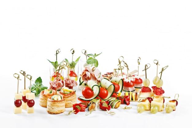 Большой привлекательный набор канапе с овощами, сыром, фруктами, ягодами, салями, морепродуктами, мясом и украшениями на белом столе