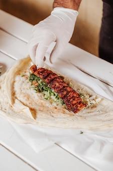 Приготовление шаурмы с кебабом и арабским хлебом.