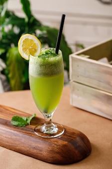 木製の背景でエレガントなガラス製品に健康的なレモンミントフレッシュジュース。メニューには本格的な料理の飲み物のオプションがあります。