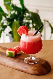 木製の背景でエレガントなガラス製品に健康的なニンジンフレッシュジュース。メニューには本格的な料理の飲み物のオプションがあります。